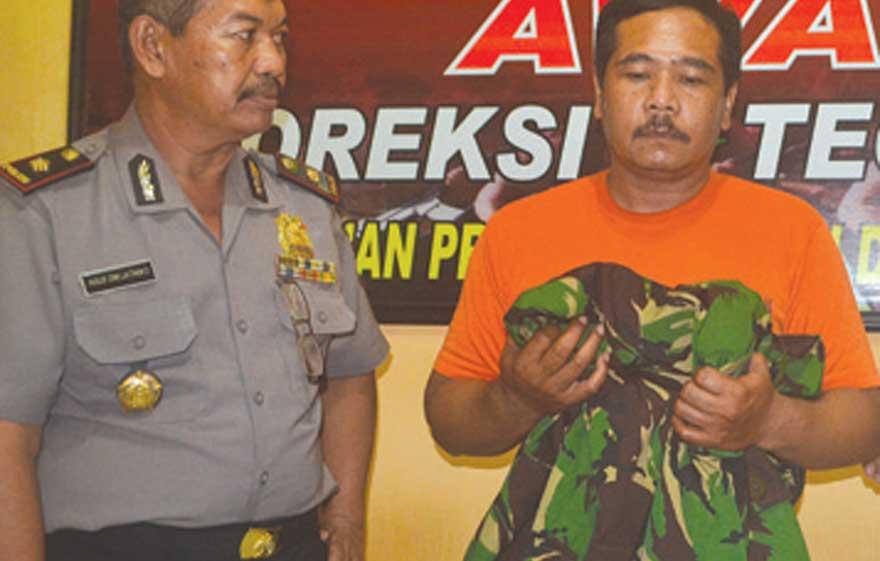 Tersangka-dengan-jaket-doreng-yang-mirip-milik-TNI-AD-diamankan-di-Polsek-Muncar-kemarin